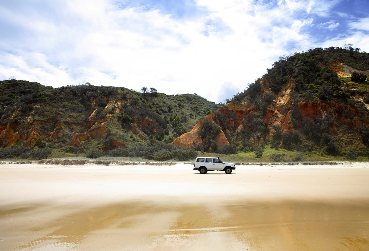 4WD passing Red Rock along 75 mile beach on Fraser Island