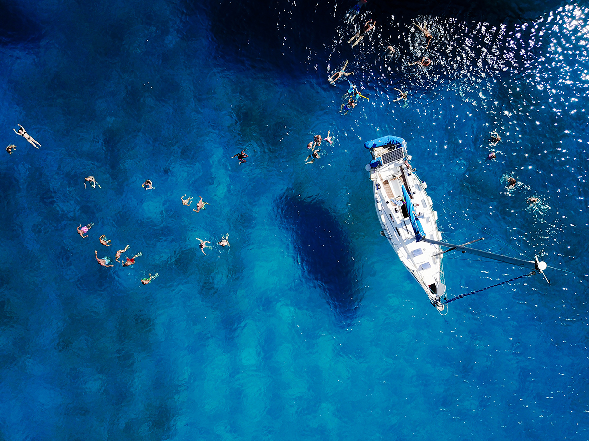 Aerial shot of beautiful blue lagoon at hot summer day with sailing boat Top view of people are swimming around the boat