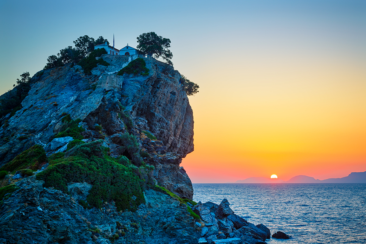 Rock with famous church Agios Ioannis Kastri on Skopelos island Greece at sunrise where scenes of Mamma Mia movie were filmed Sun raises above Alonissos island