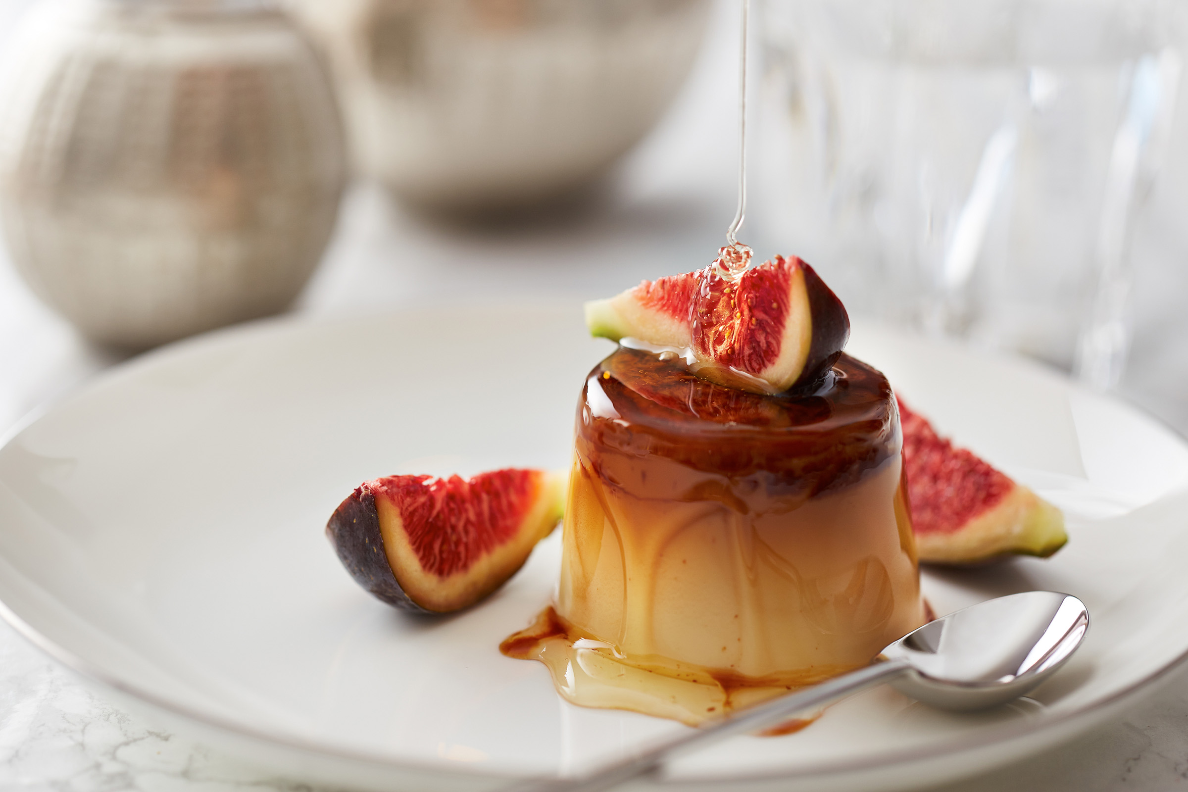 Pouring honey on fig and pudding