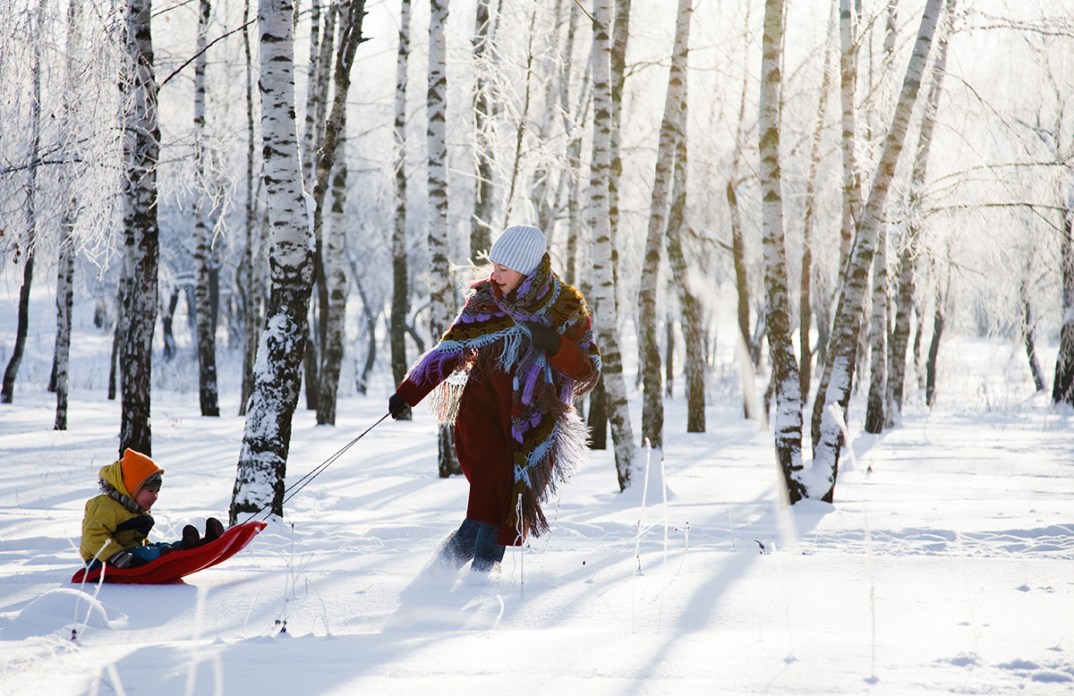 family having fun in winter running with sled