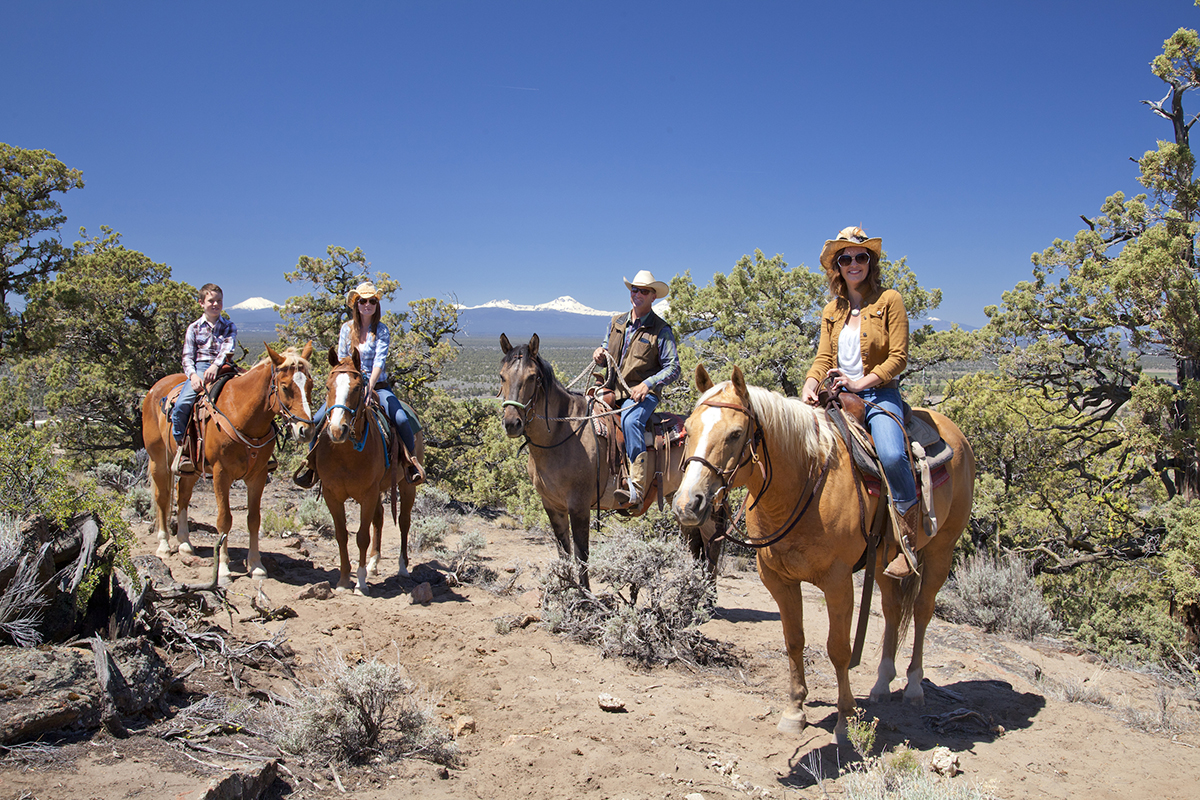 family on horseback at a ranch