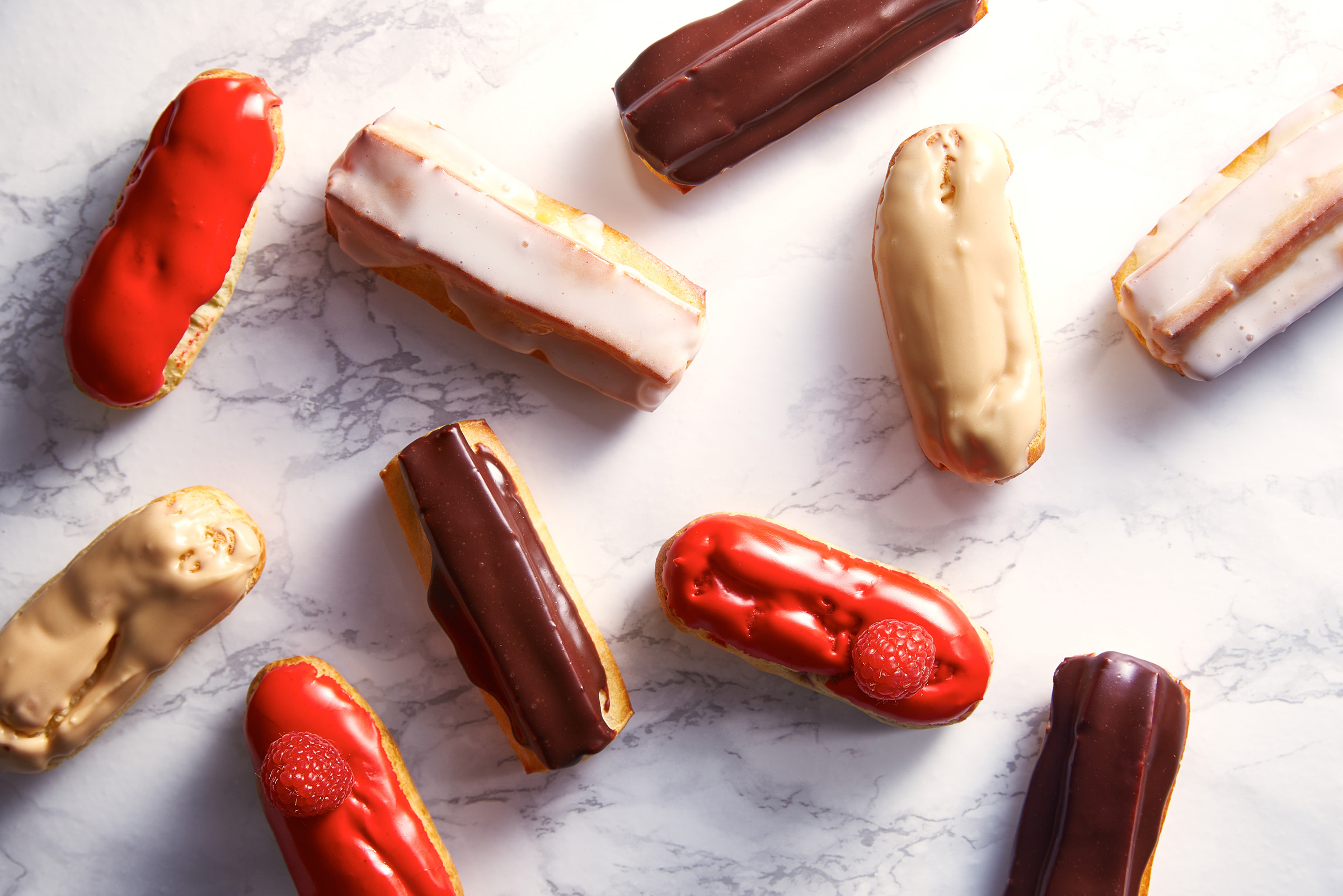 Variety of eclairs on marble background