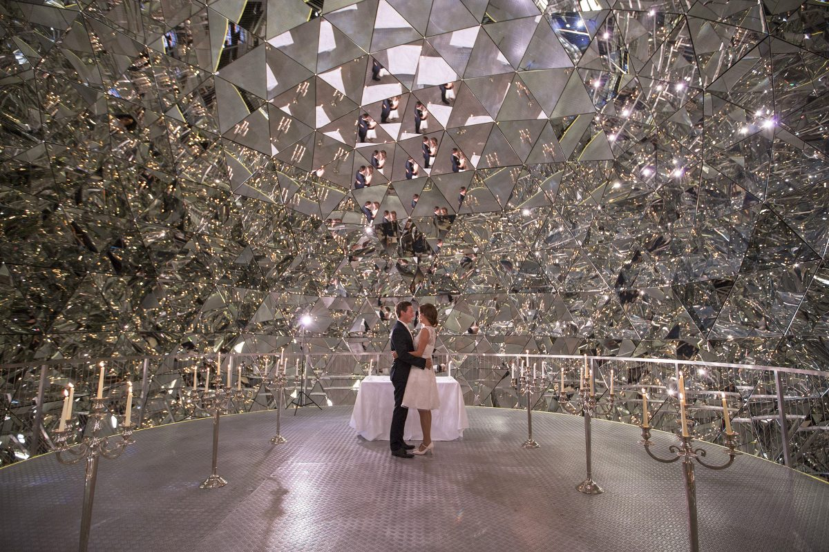 couple standing in a sparkling mirrored room