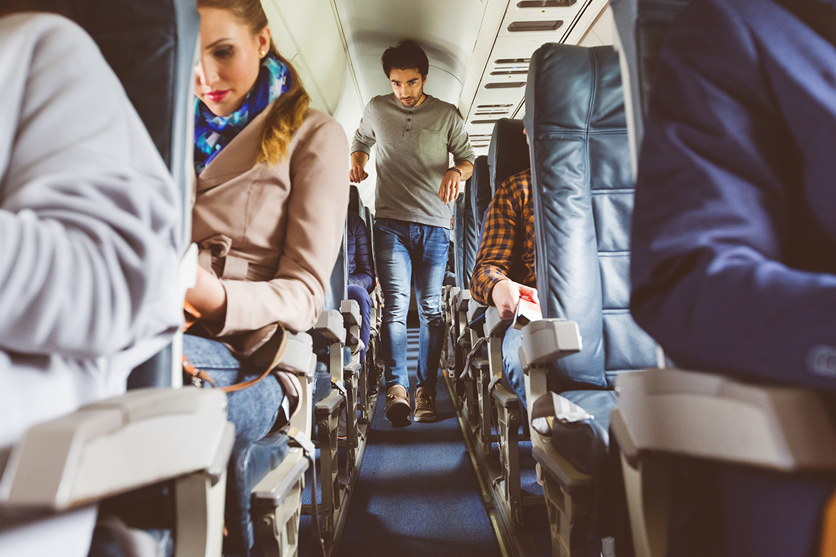 Passengers on seat during flight with man walking in aisle