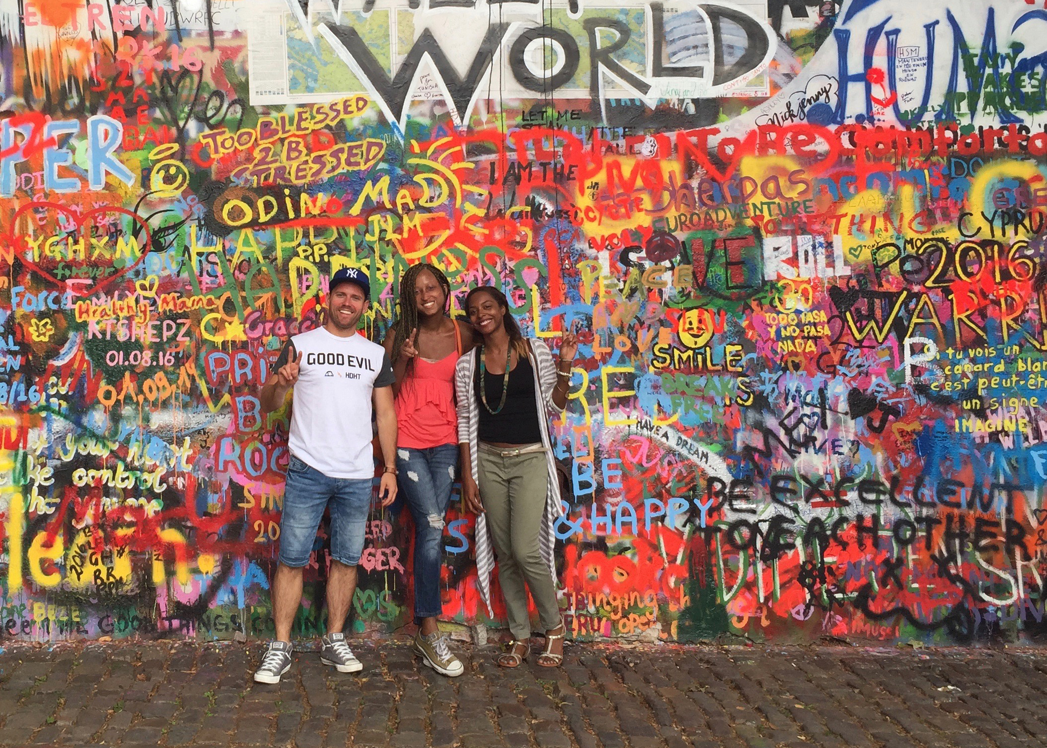Friends standing in front of Lennon Wall in Poland