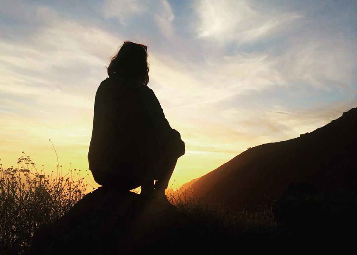 Girl watching the sun set on Big Sur coastline